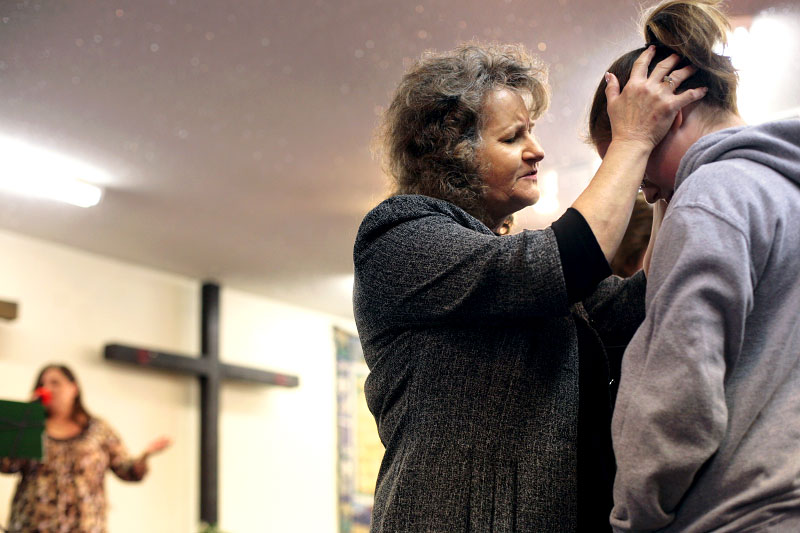 Linda Kelley, wife of Pastor Don Kelley, prays with another parishoner at Vienna Christian Life Assembly & Academy during Sunday morning service.
