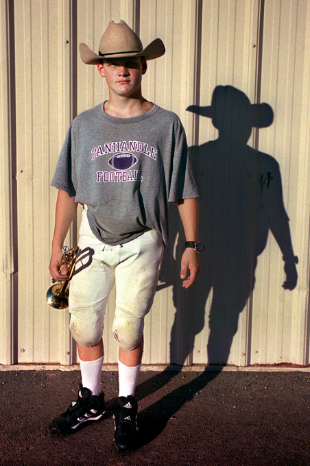 After football practice at Panhandle High School, a player dons his hat and grabs his trumpet before heading back to the field for band practice. Panhandle is a town of about 2000 residents located 45 minutes from Amarillo, Texas.