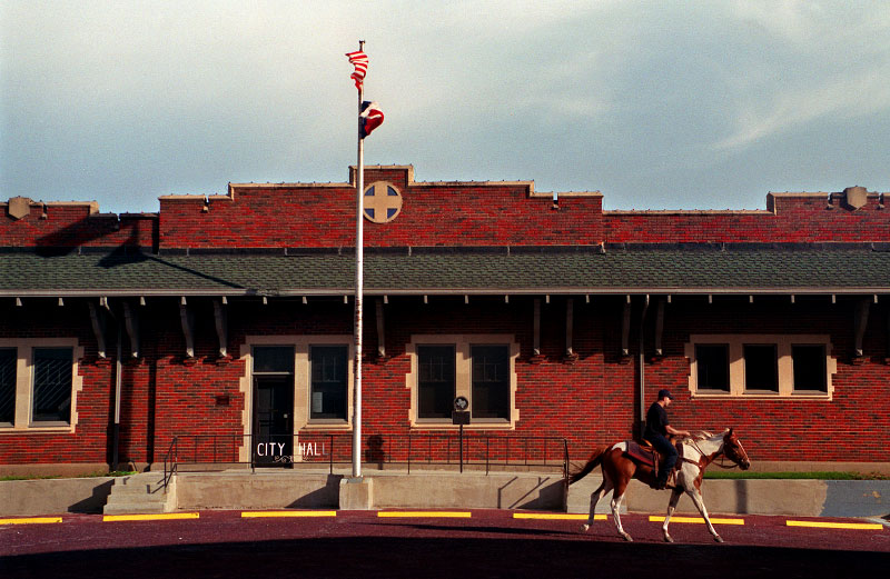 A man rides his horse past City Hall in Panhandle, Texas.