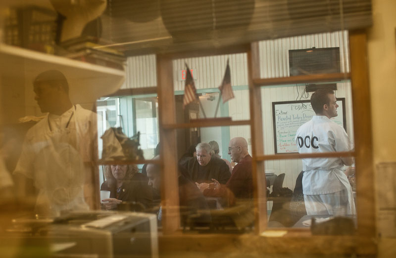 In reflection at left, Calvin Hodge, in the second week of a five week rotation as head chef, prepares lunch at the Fife and Drum Restaurant at the Northeast Correctional Center in Concord, Mass. At right is inmate Mark Molina serving customers.