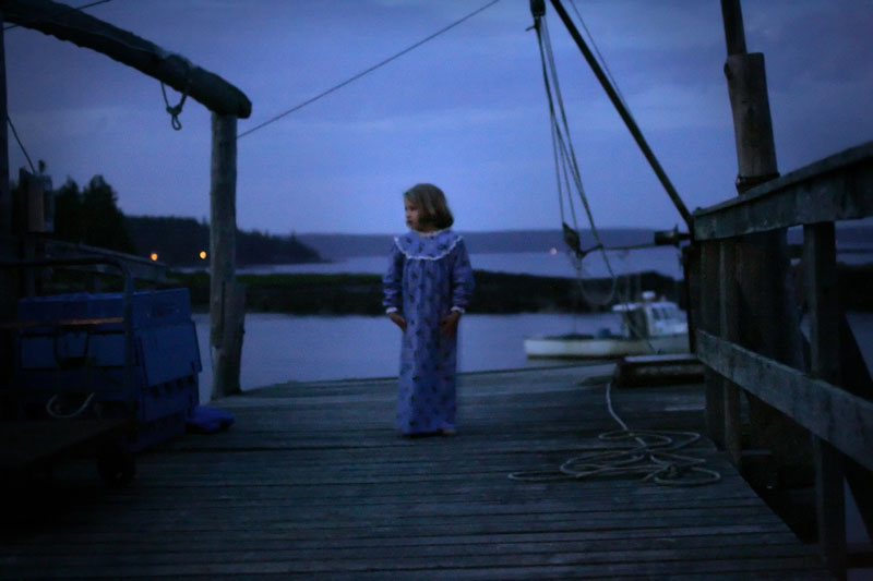 Portrait ofAnna Ludlow, 7, on the dock at Hiram Blake Camp in Harborside, Maine.  Anna is the daughter of Deb and Dave Ludlow who own and operate the camp and often becomes a temporary member of whichever group is visiting the camp.  {quote}This place is more than just a vacation destination,{quote} Deb Ludlow said.  {quote}They (visitors) get the sense that this place only exists when they are here.  It is just for them.{quote}