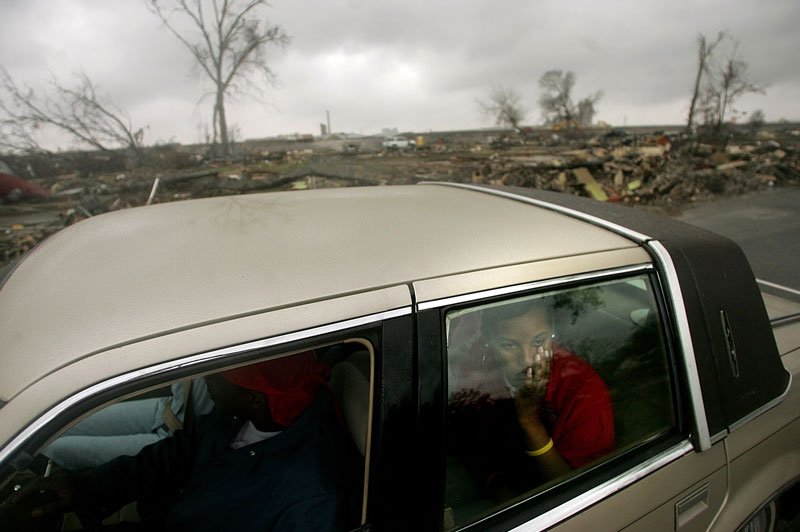 Members of the Berryhill family (who did not want to be identified by their first names) stare out at the devastion of their old neighborhood in New Orleans' Lower Ninth Ward, Tuesday January 17 2006.  Directly behind their car is the lot where the Berryhill's home used to sit until the levee protecting the neighborhood was breached by flood waters from Hurricane Katrina sending a wave of water into the neighborhood and destroying their home.