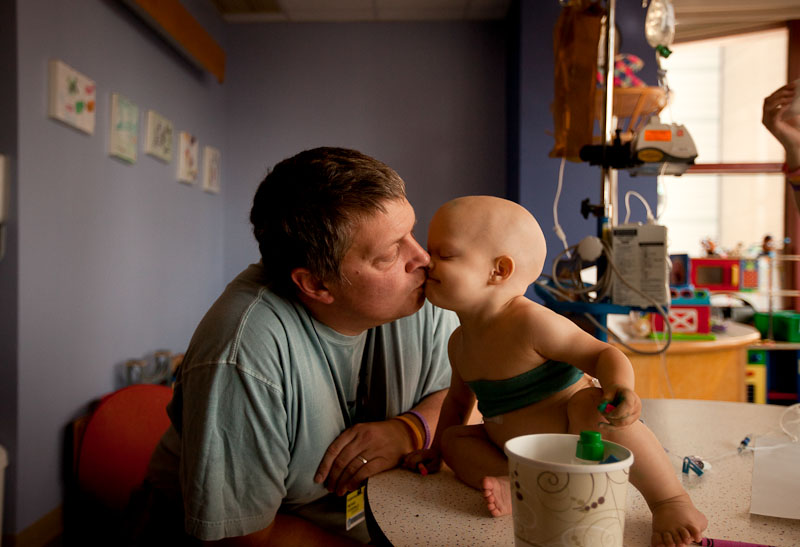 Mike Fitzgerald and his daughter Saoirse share a kiss while drawing at Children's Hospital Boston, August 25, 2011. Both Saoirse and Fitzgerald's wife Kezia are undergoing treatment for two unrelated forms of cancer. Faced with two family members getting cancer at the same time, Mike Fitzgerald said there isn't much you can do to make sense of it. {quote}It is so overwhelming you just kind of ignore it,{quote} Mike said. {quote}You just have to focus on getting better,{quote} Kezia added.