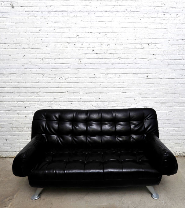 Black couch against white cinderblock wall in storage unit in Hoboken, New Jersey. By photographer Adena Stevens