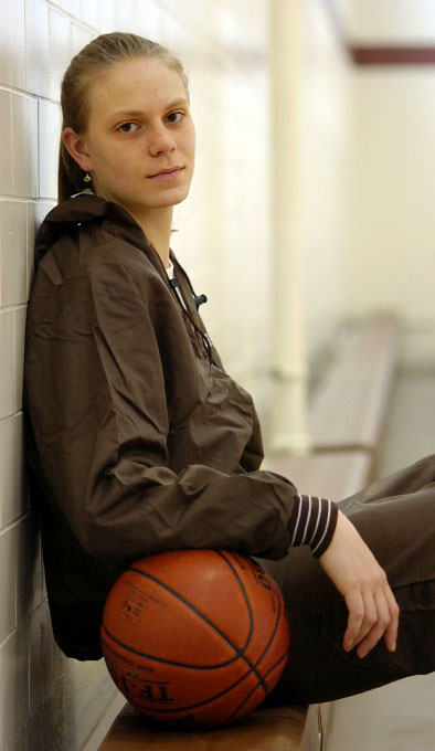 Portrait of basketball player Heather Buck, sitting in a gym with a basketball. By photographer Adena Stevens