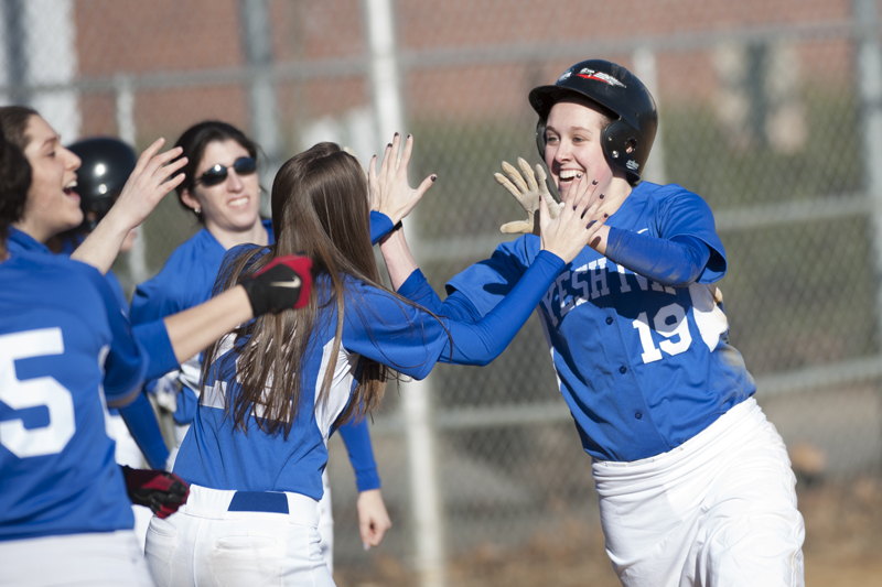 Yeshiva University's softball team celebrates as runner scores