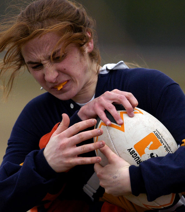 An Ithaca rugby player tries to keep both hands around the ball, even as a Syracuse player tries to get it from behind at the Blue Balls tournament in Watertown, NY. By photographer Adena Stevens