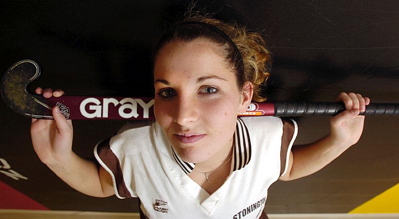 Portriat of field hockey player Liz Bolduc holding a field hockey stick. By photographer Adena Stevens