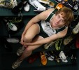 Portrait of runner Jason Cusack surrounded by dozens of running shoes. By photographer Adena Stevens