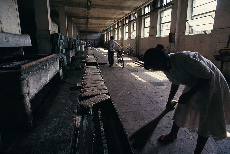 A woman sweeps the floor of a bread factory in Tirane, the capitol of Albania.