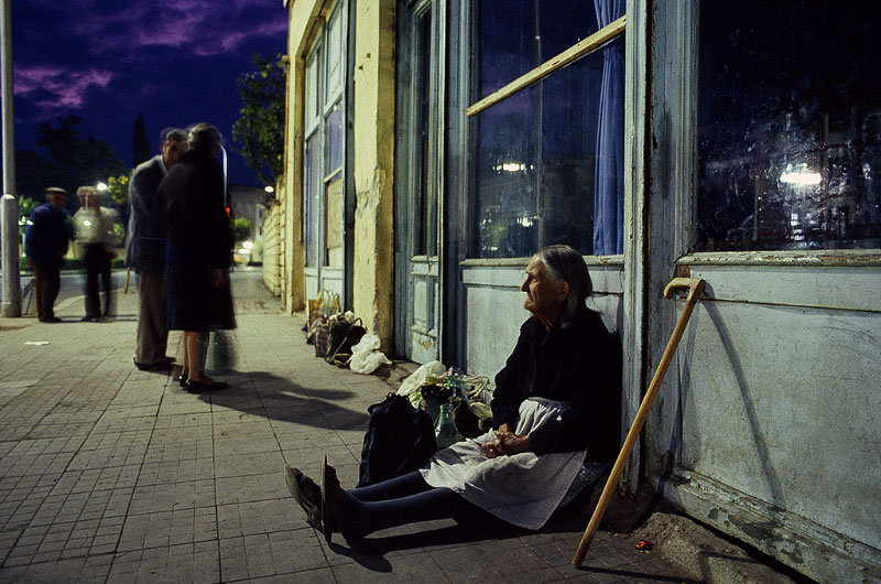 A woman sits on the sidewalk saving her place in line, waiting for a milk delivery. It is pre-dawn in Tirane, the capitol of Albania. Food has become scarce due to the collapsing government and the breakdown of system.