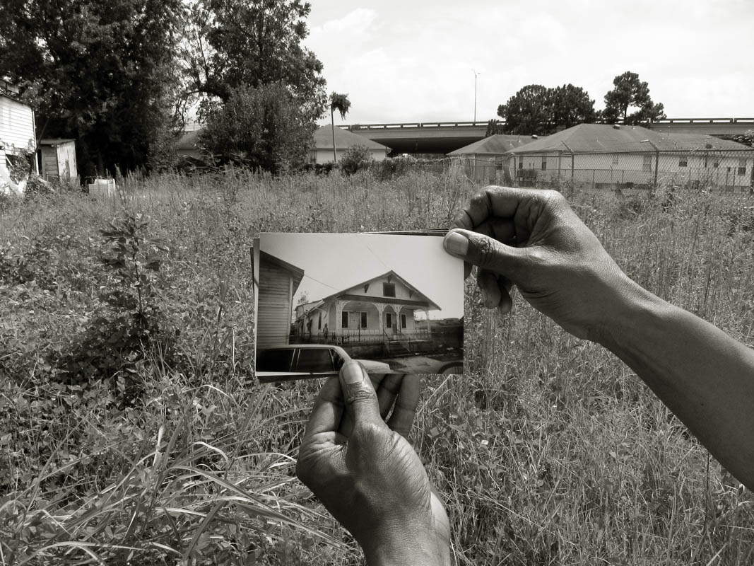 A portrait of Michael Dupont,59, standing near the overgrown lot where his great grandfather used his WWI pay to buy a house, and where his grandfather lived, and where his father and mother made their home; he holds a photo of the house that used to be. Because of miscommunication during the process of applying for Road Home assistance, their house was demolished unbeknownst to them and they recently received a bill from the city for the work.