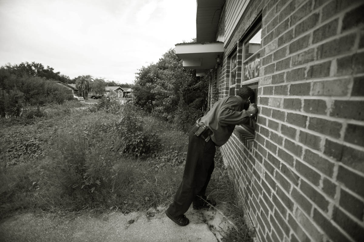 A portrait of community leader Aaron Broussard, resident and member of the East Shore neighborhood association concerned for his neighborhood and the blight he is seeing from absent residents and overgrown properties. He looks through a window of an empty house that still has debris from Katrina inside.