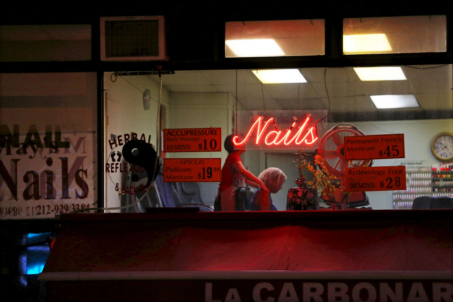 Late evening scene of a nail salons located alongW14th Street NYC. A customer gets a neck massage while her nails dry.