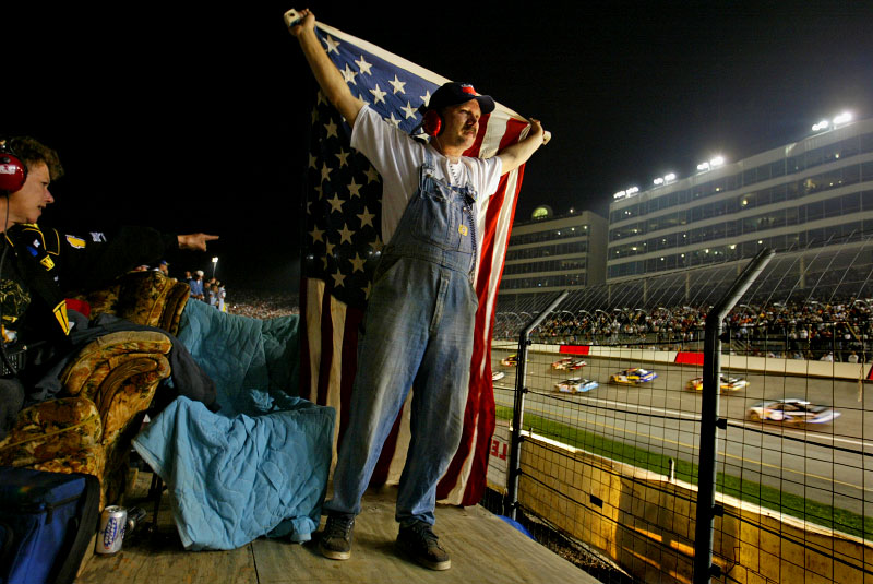 {quote}The Couchman{quote} Bill Montgomery follows tradition of setting up his scaffold in center track at NASCAR races with a living room setting; lamps, a couch; so friends and family can watch the race in the comfort of home. He also traditionally drapes an American flag around his shoulders as the race begins for all the drivers to see.