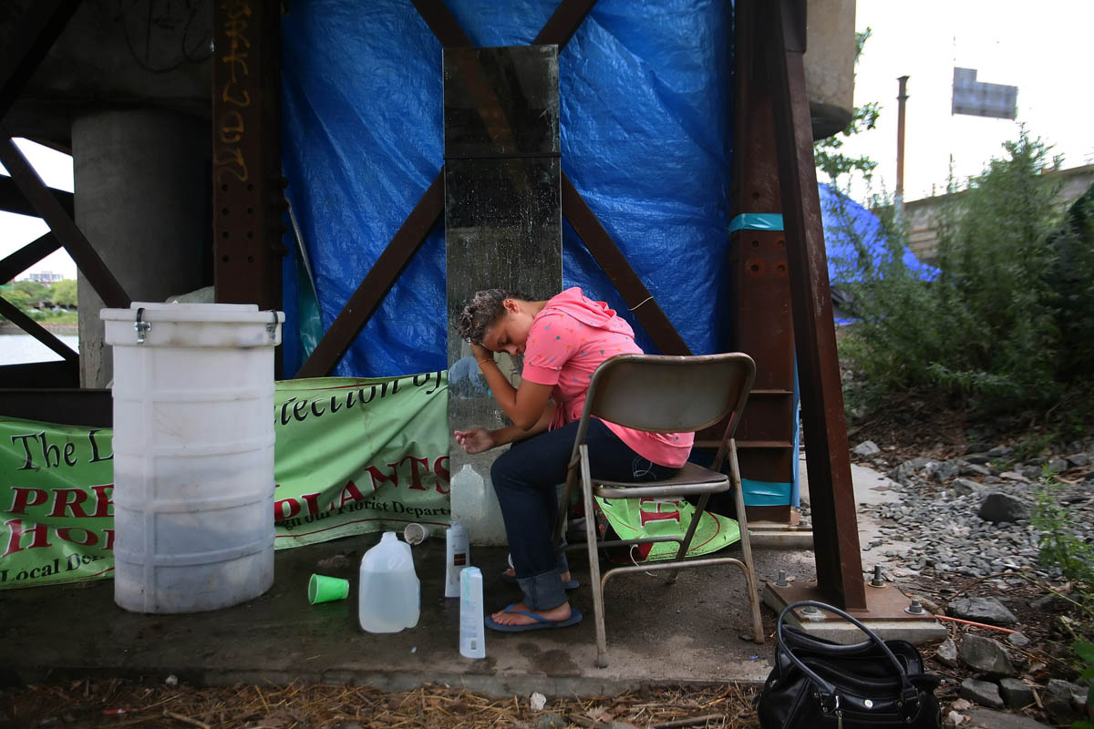 A tent city, dubbed Camp Runamuck by a community of homeless residents living in tents under a now closed overpass stretch of route 195 that is about to be torn down. Stephanie Proulx,19, shampoos her hair near the camp's restroom.