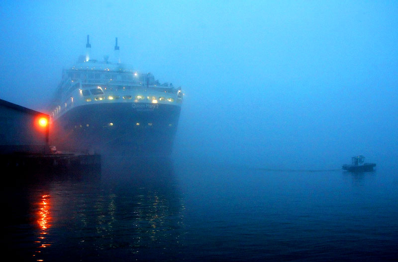 The Queen Mary II docks in Red Hook Brooklyn. 5am fog surrounds the scene as a patrol boat secures the area.