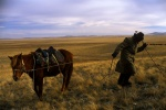 A sheepherder in Kazakhstan pulls on his horse as it tries to eat the grass 