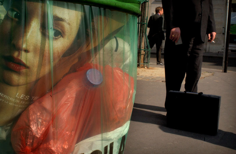 A woman on the back of a fashion magazine stares out of a trash bin in Paris.