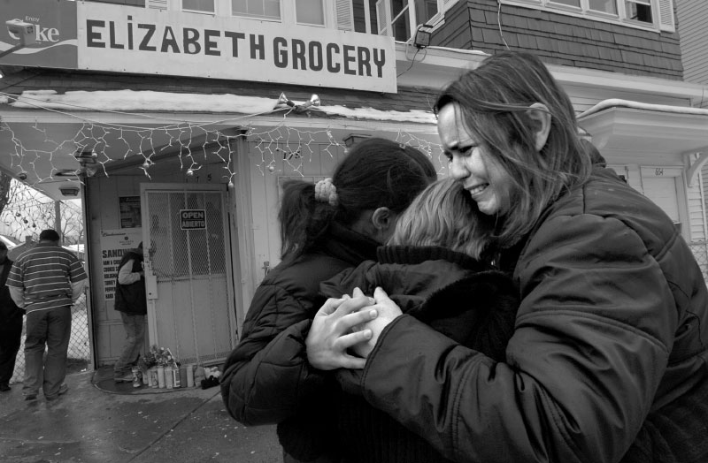 Telma Diaz, right, hugs her daughter Paloma Batista outside the store in Hartford, CT where Diaz's nephew, Enrique Miguel Perez Diaz,  was shot the night before.  Behind them are candles and stuffed animals for a make-shift memorial at the site.