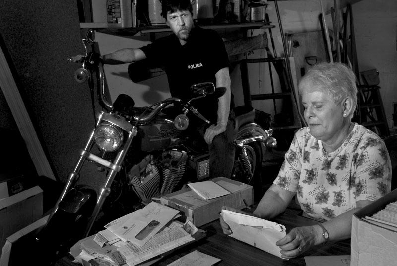 Volunteers for the Polish Genealogical Society gather inside the garage of Jonathan Shea, left, to sort through documents that will help form a genealogical database of Polish lineage.   When all the chairs in his garage were taken by volunteers, Shea sat on his motorcycle.