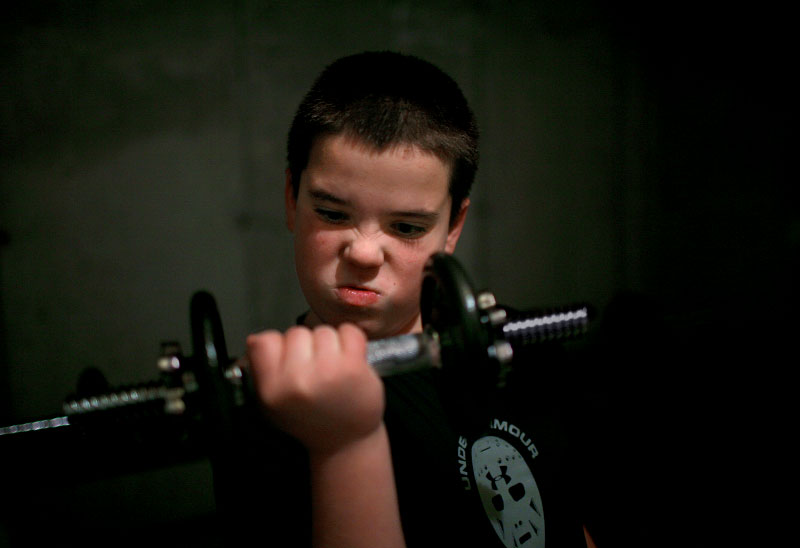 Nate Bleszinski (11) does bicep curls in his basement work-out-area.  Nate is trying to lose weight and gain muscle through exercise and nutrition.  He will often do extra curls and sit ups even when he has already reached the required number.
