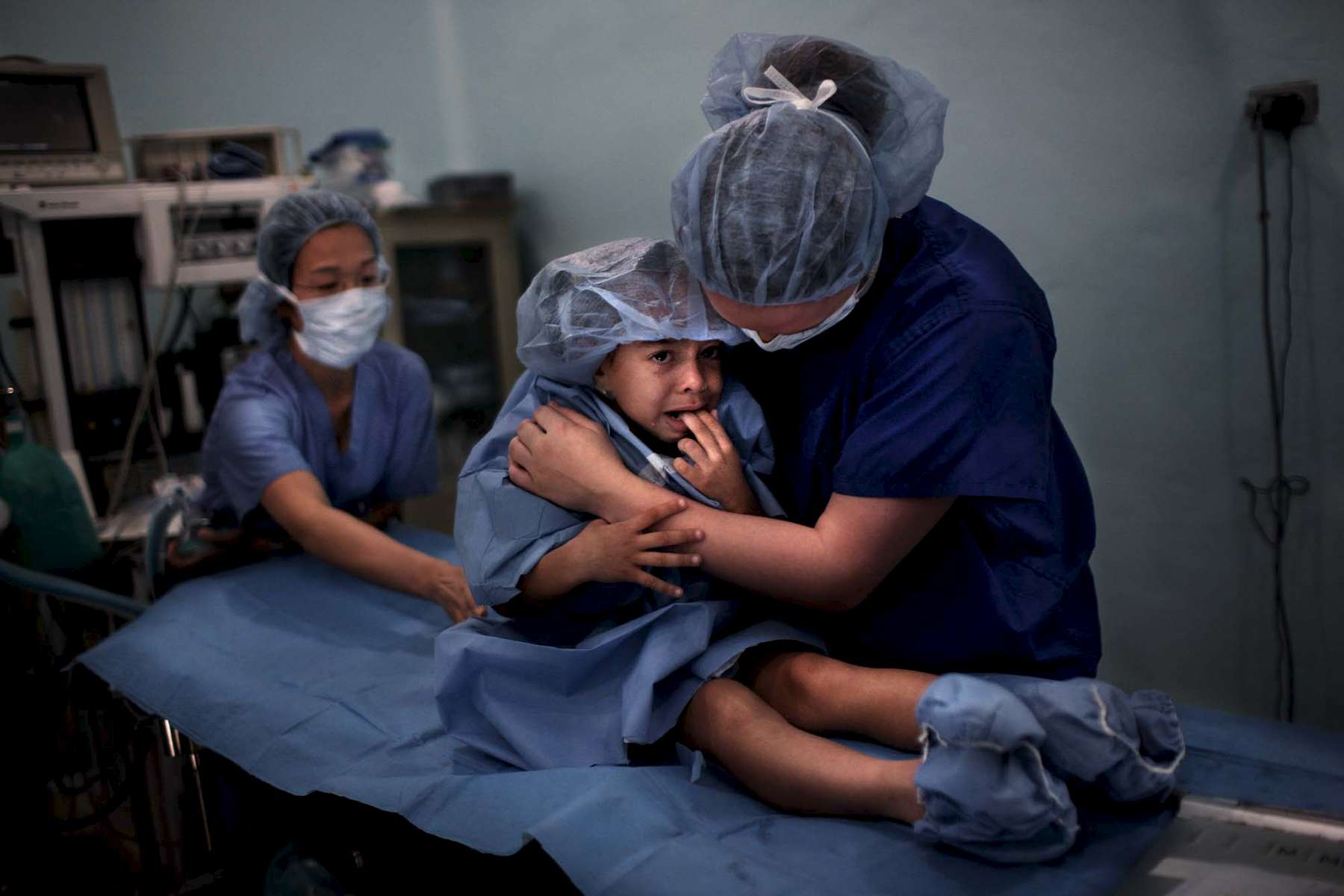Tiffany Ellison comforts a frightened Daphne Rodriguez before a hernia operation. At left is Grace Moy, an anesthesiologist, who will put her asleep for the surgery.
