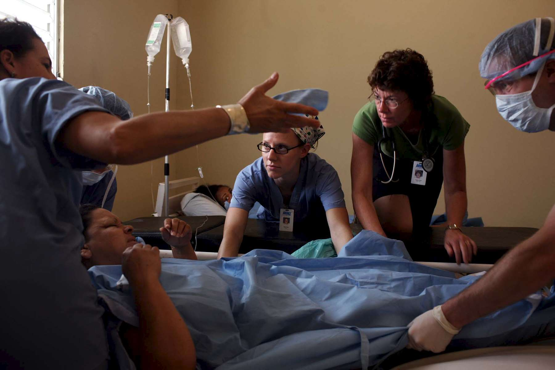 Nurses Sally Jones, center, and Caren Evans help move a patient into the recovery room after surgery. At right is Kevin Krebsbach.