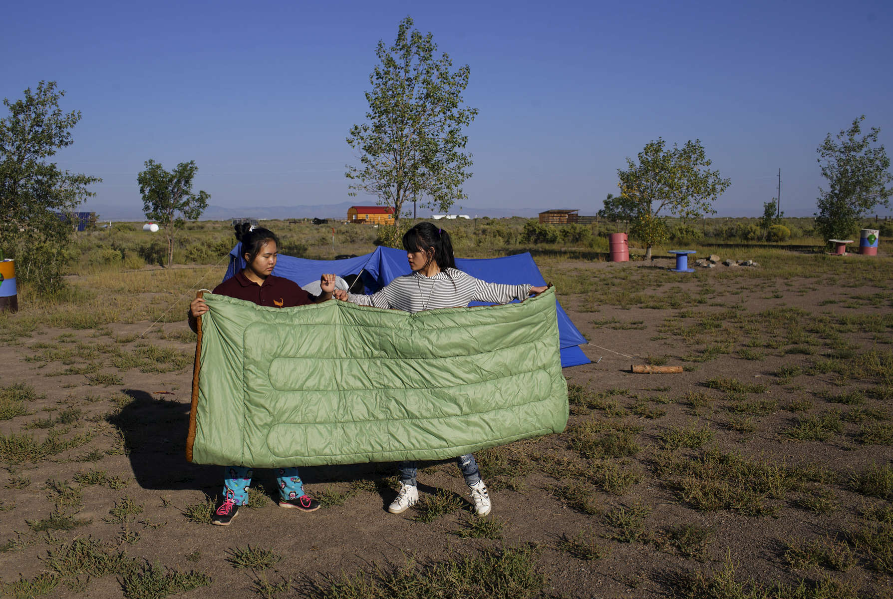 Shrostina Magar, 14, left and Puja Rai, 14, right, unfurl a sleeping bag before placing it in their tent at their campsite in Hooper, Colo. on Sept. 2, 2017.
