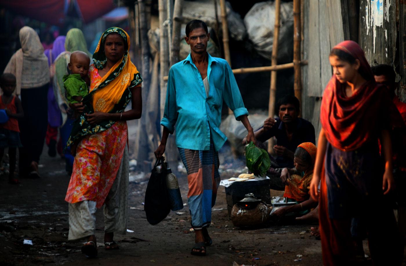 Nizam Hawladar walks through the slum area outside of his home.