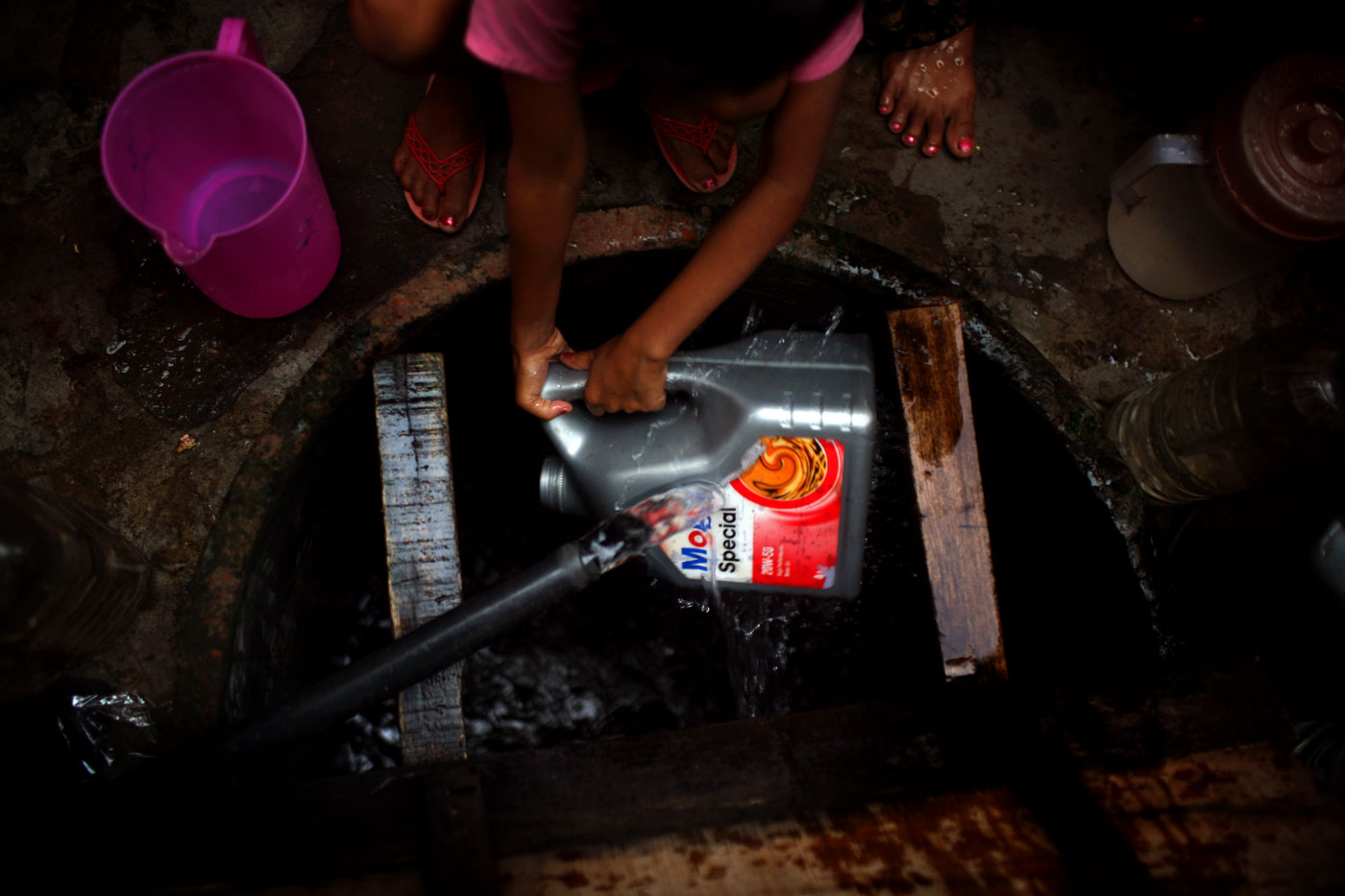 Nipa Hawladar washes out an oil container which will be used for carrying water for them to cook with and to drink from.