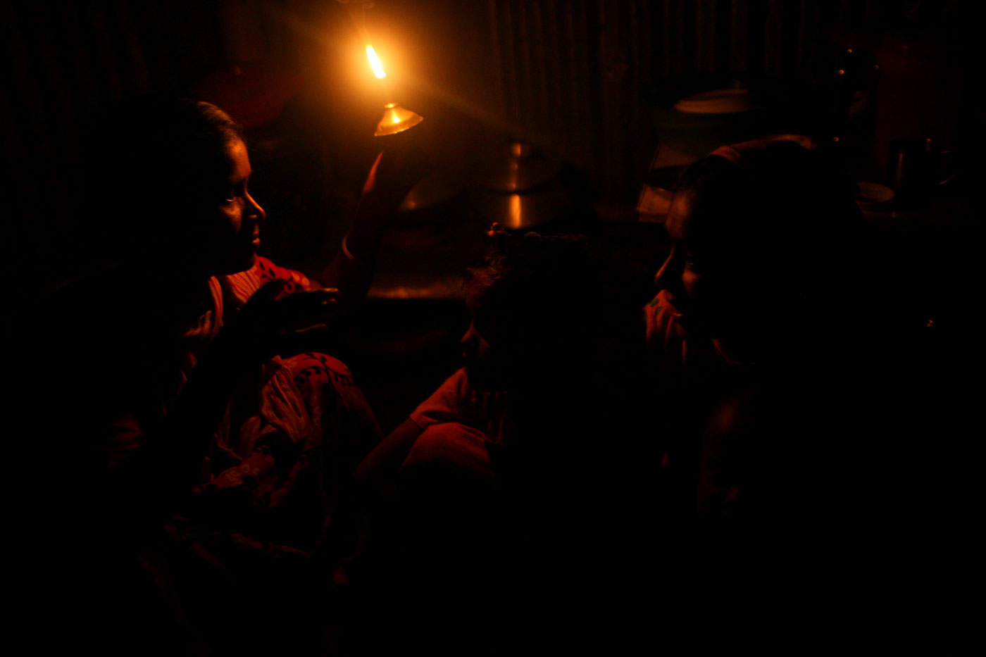A single lamp provides Mahe Noor light during a power outage. Noor hopes that someday their lot in life will improve and they can leave the slum.