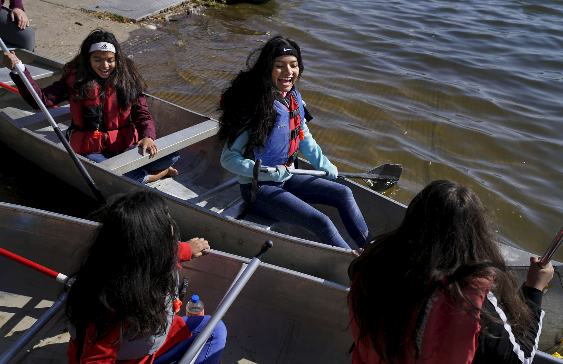 Susmita Adhikari, 16, upper left, and Laxmi Adhikari, 14, center, are all smiles as they canoe for the first time at the Bear Creek Reservoir in Lakewood, Colo. on Oct. 14, 2017.