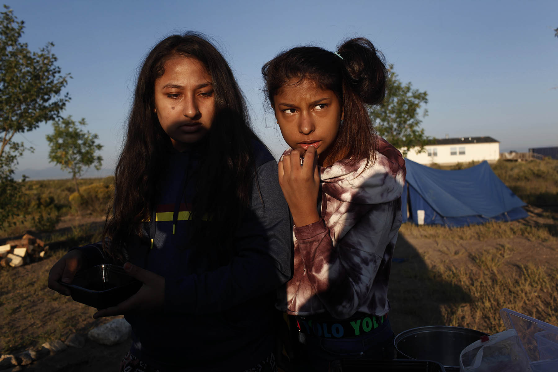 Nirshika Neopany, 14, left and Sostika Chhetri, 14, right, pause before making breakfast at their campsite in Hooper, Colo. on Sept. 2, 2017. It's not far from the Great Sand Dunes National Park and Preserve, where they would later visit for the first time.