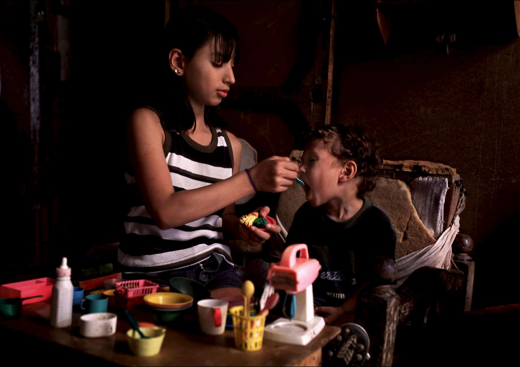 A brother and sister pretend to play house in their home which is constructed of tin walls, dirt floors and used furniture in a slum area outside of San Jose.