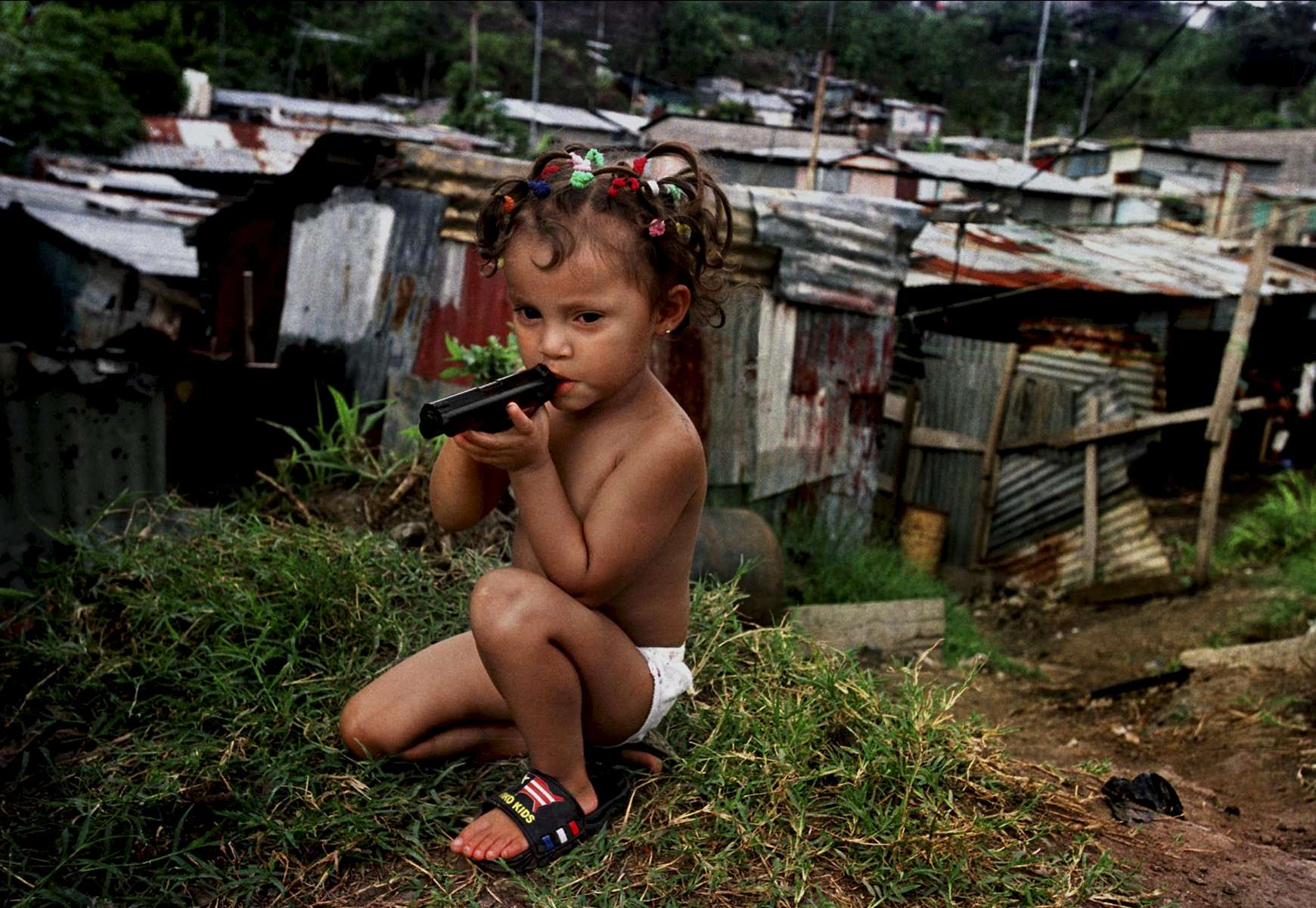A girl plays unattended in La Carpio one afternoon on a hill overlooking the village. La Carpio is a Nicaraguan refuge community just outside of San Jose which is considered one of the most dangerous areas in Costa Rica.