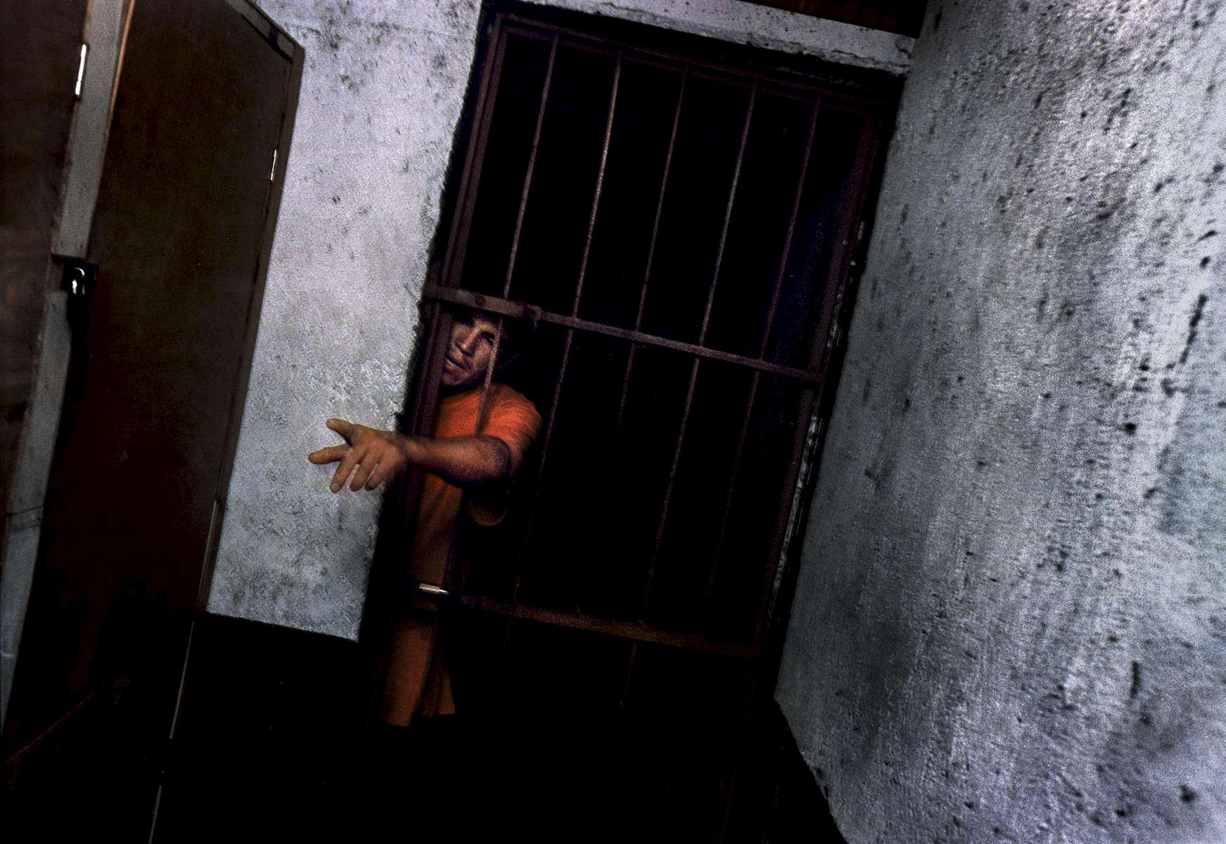 A man cries out to be released from jail after being arrested for public intoxication in La Carpio. The jail is a one-room area with no beds and no lights, and like many jails in Central America, is poorly maintained.