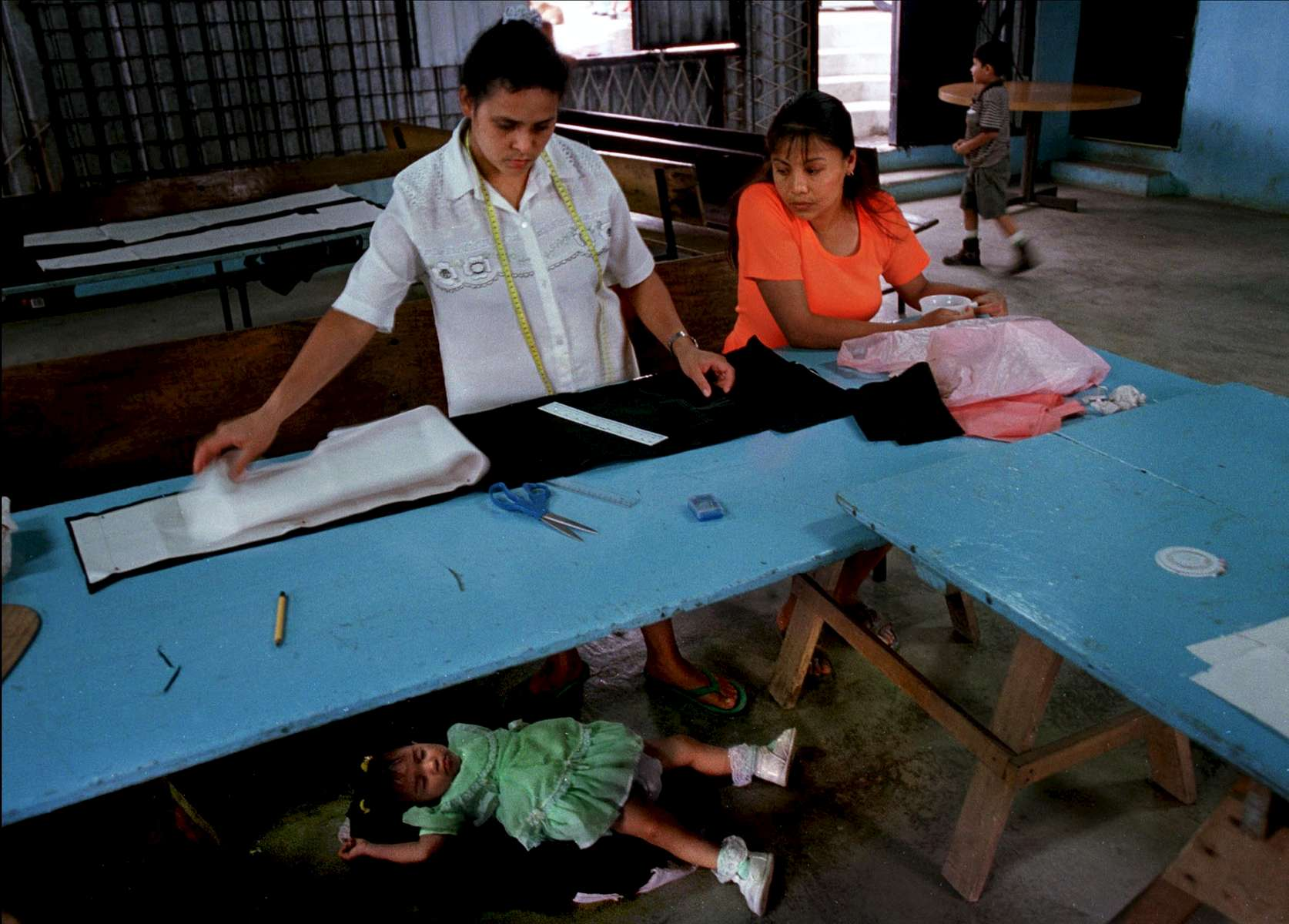 Two women work to sew their own clothes while the daughter of the woman at left takes a nap in La Carpio. Most families in the community can't afford to pay for someone to take care of their children while they work.