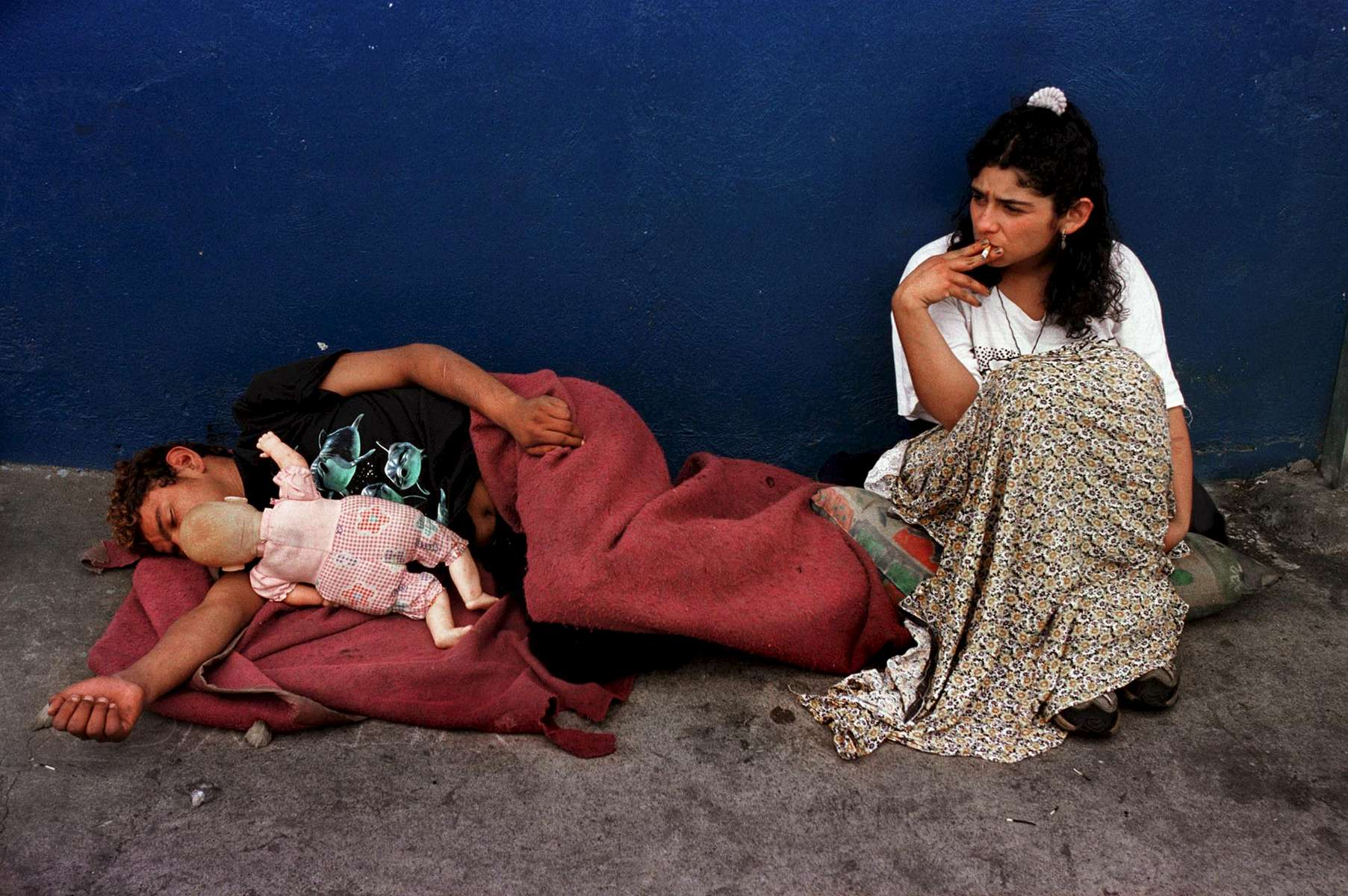 A young man strung out on drugs is passed out while holding a baby doll on the streets of San Jose. At right is his girlfriend. Teenage drug use is rampant by those living on the streets of the capital city.