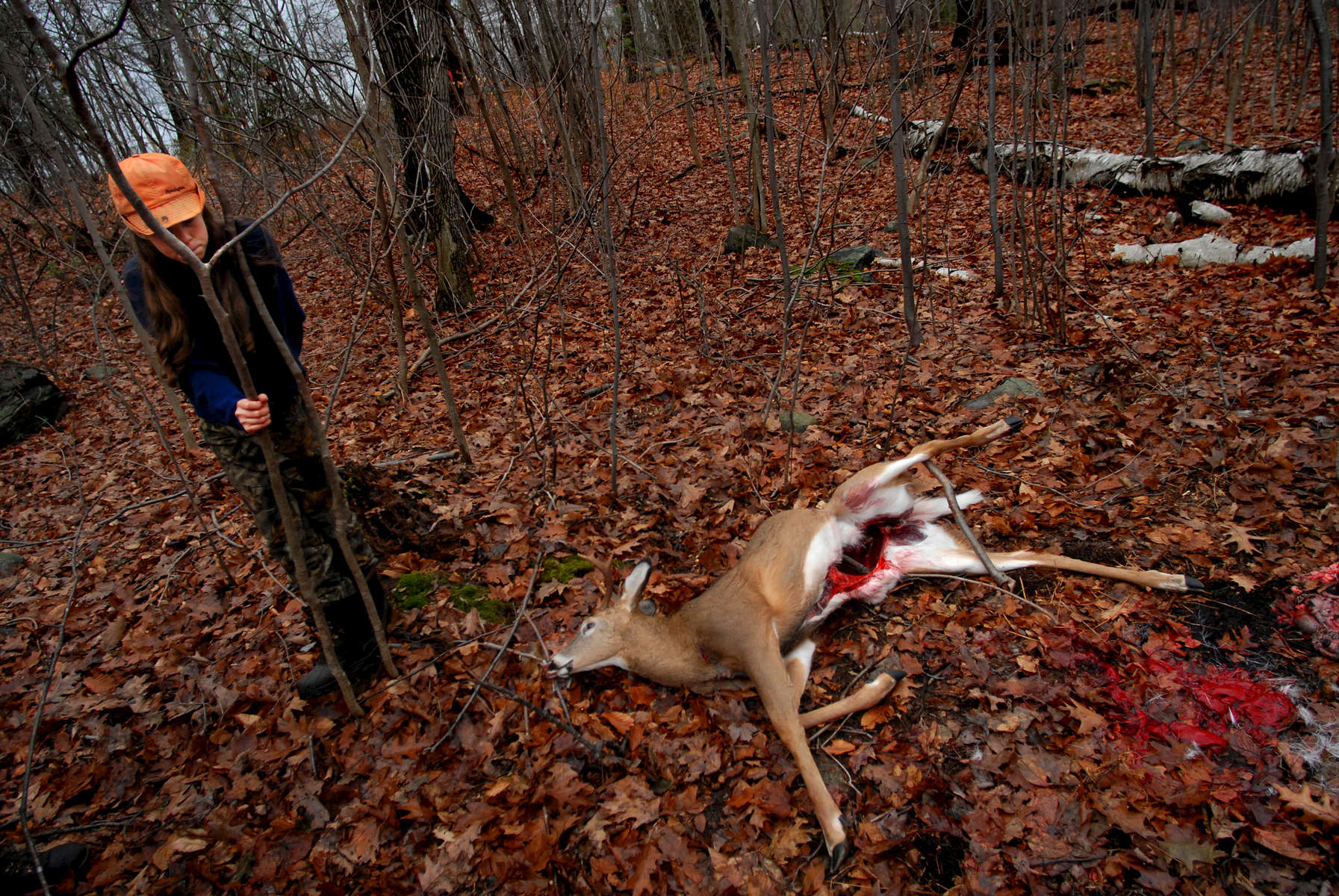 It's an emotional sight for Beth Irwin, 13, as she stands by a deer that had been recently shot on opening day of hunting season. Irwin was out hunting with her father, Tim, who was passing on the tradition of hunting to Irwin.