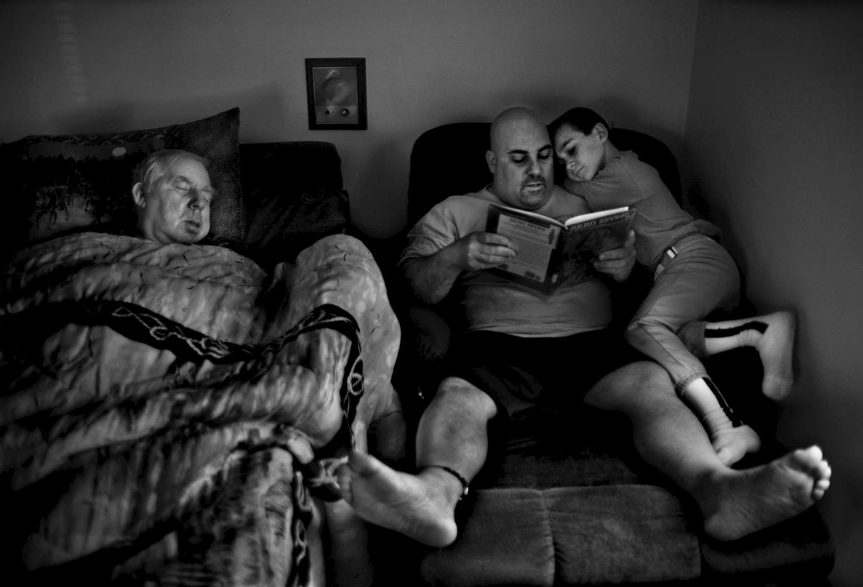 Jim Kennedy reads to his son, Elijah, before his baseball game. At left is Kennedy's father, William, who is dying of cancer. Kennedy is a single father who is taking care of both son and father at the same time.