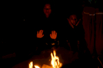 Susmita Adhikari, 16, center and Devika Subba, 14, right,  keep warm by the fire during a campout at Bear Lake Campground in Lakewood, Colo. on Oct. 14, 2017.