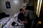 Mike Morin bends to kiss his wife, Gloria, before tucking her into bed. The two have been married for almost 30 years.