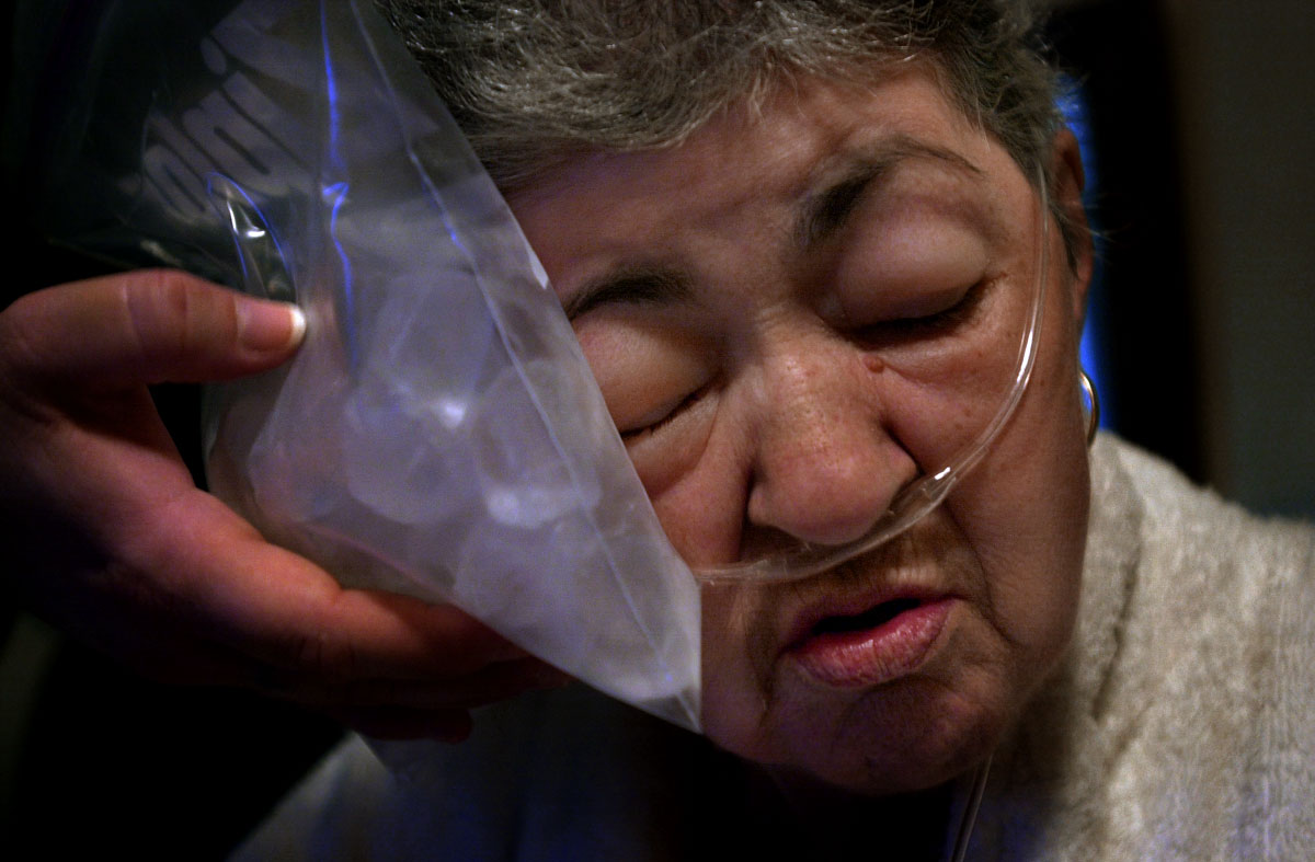 Gloria's daughter Sharon holds an ice-pack to her face ion order to keep some of the swelling down. As the cancer spreads, her body's ability to process fluids diminishes and in return retains more.