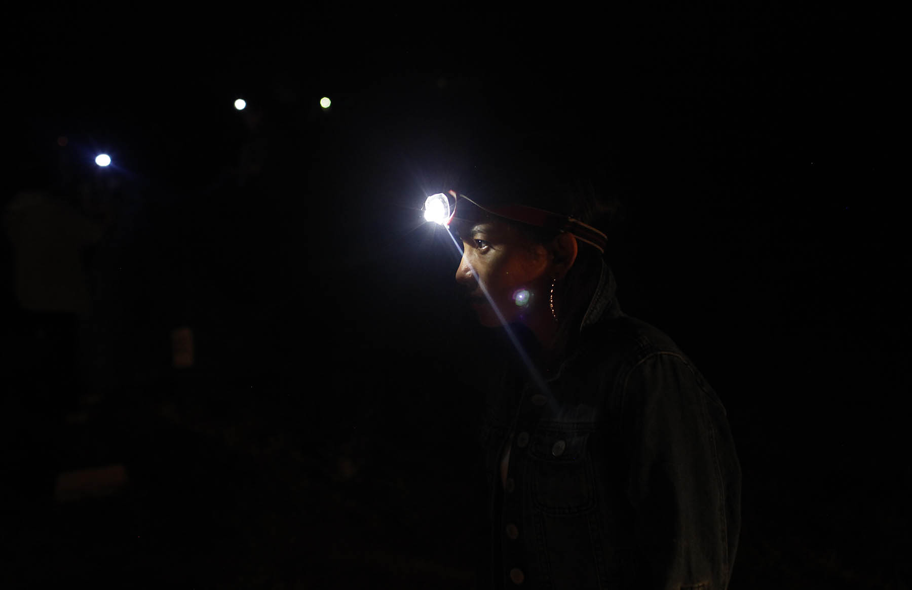 Sapana Gurung, 14, uses her headlamp to light the way at night at their campsite in Hooper, Colo. on Sept. 2, 2017.  In the background are other headlamps used by the girls.