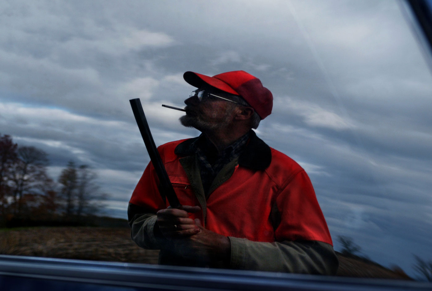 Barry Wahl is seen in a reflection of his brother's truck as he pauses before heading out to hunt.