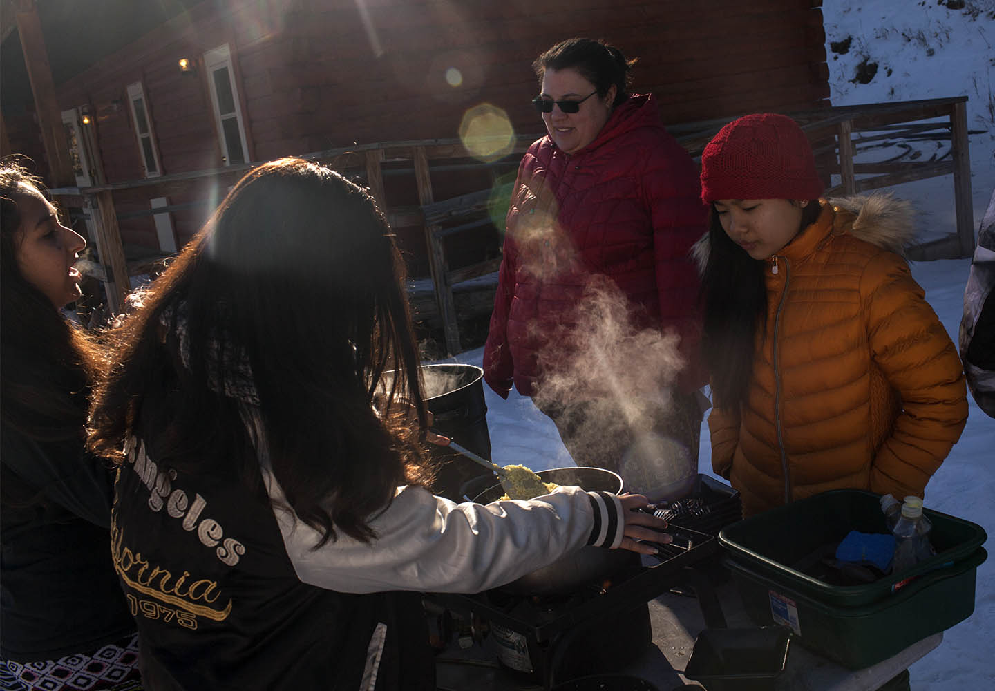 Nirshika Neopany, 14, left, Sapana Rai, 14, middle, Jamie Stanley, 33, and Susmita Limbu, 14, right, prepare breakfast at Camp Alexander at Lake George, Colo. on Feb. 17, 2017. The camp is run by the Boy Scouts of America.