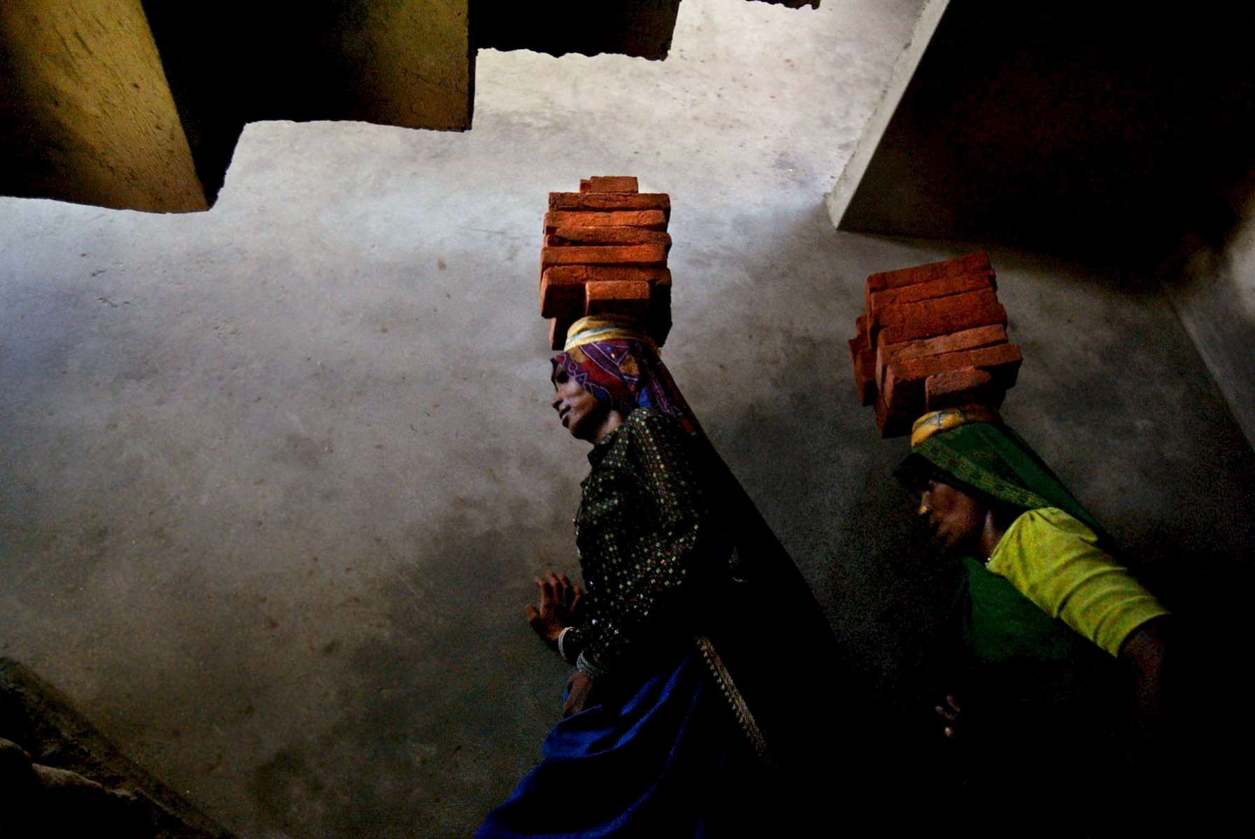 Rajasthani women carry bricks that will be used in construction in a house. Women commonly work as laborers in India.