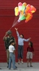 A child reaches for balloons held by a member of the Indian military during India Independence Day festivities.