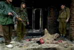 Indian military forces stand guard over a militant that was killed in a gun battle in the outskirts of Srinagar.